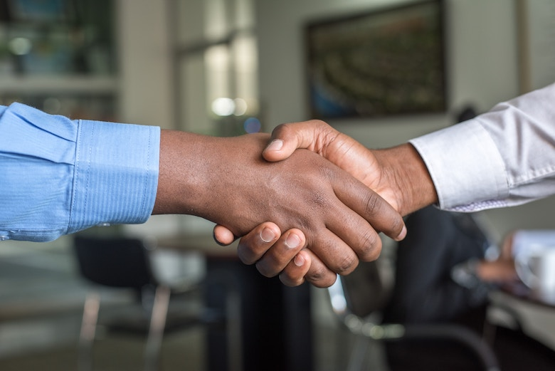 Two men shake hands in an office-type space.