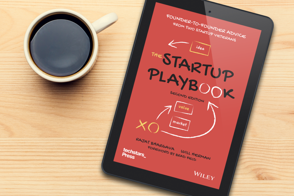 electronic version of book titled The Startup Playbook with red cover on an ipad next to a cup of coffee